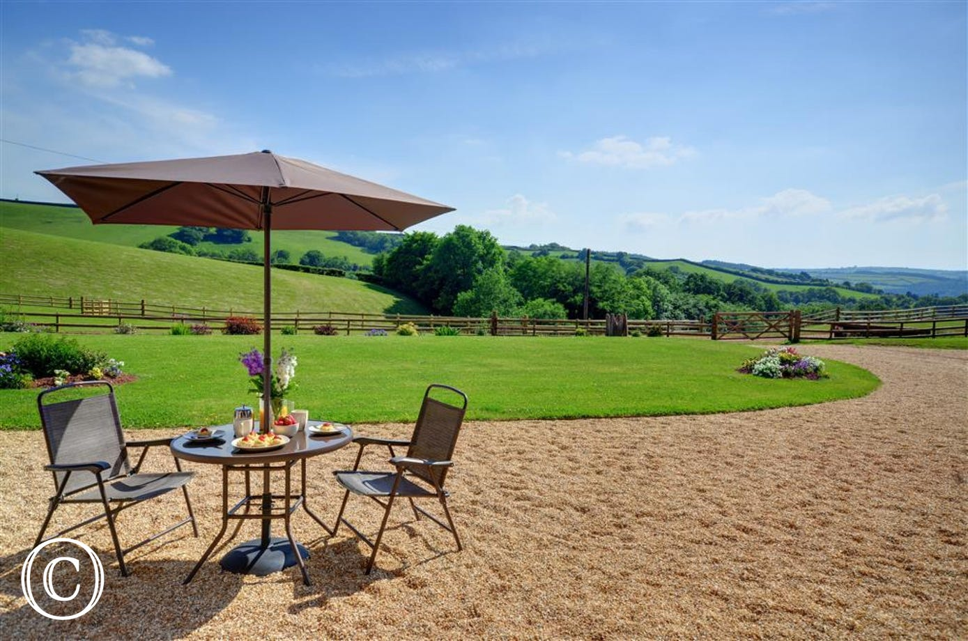 Overlooking the shared front lawned garden, each cottage has an individual patio with garden furniture