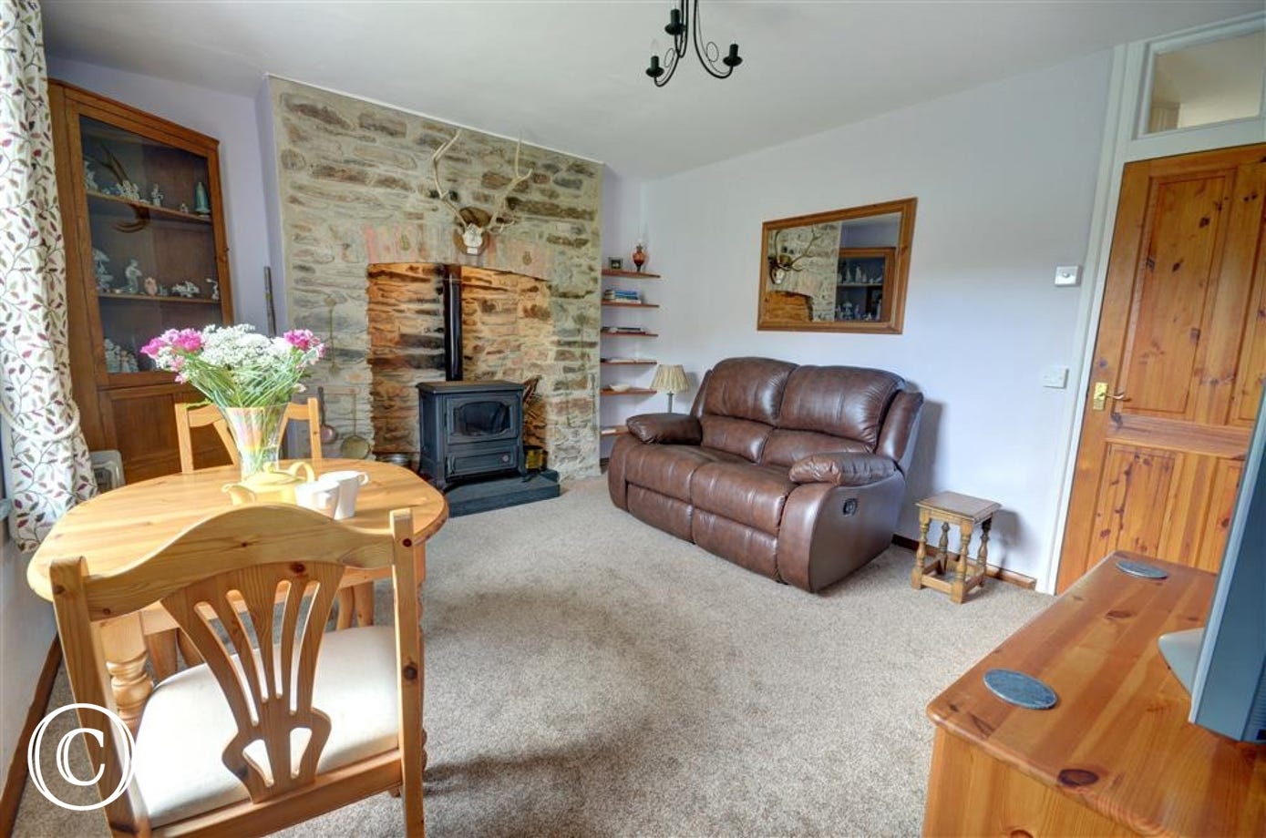 Comfortable reclining settee and an oil stove fire in the stone fireplace for those cooler evenings