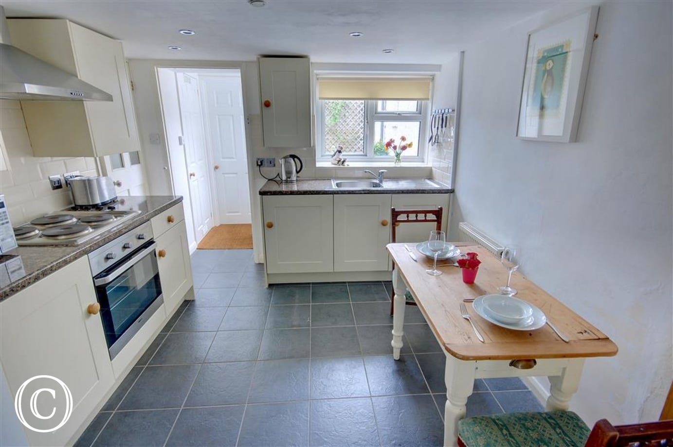 The cream country style kitchen is complemented by attractive grey slate flooring
