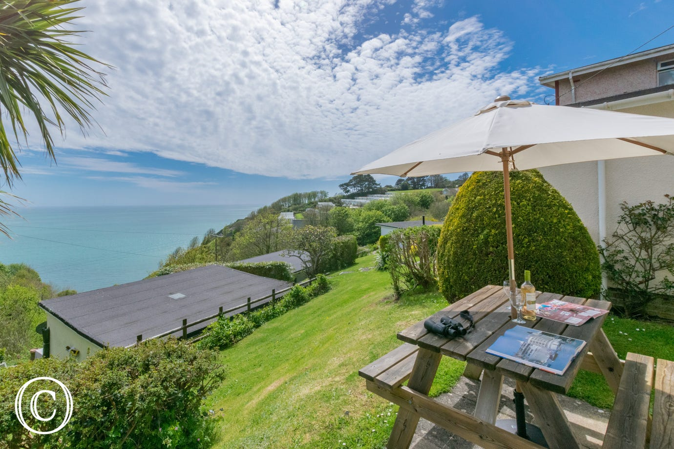 Outside: Paved patio area with picnic bench and sun parasol, perfect for 'al fresco' dining to make the most of the sea views.