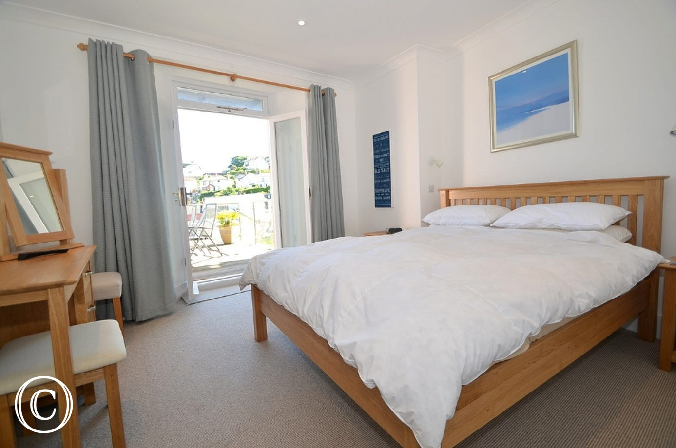 First floor, master bedroom: Double patio doors leading out onto the balcony, double bed, double built in wardrobe, dressing table, Freeview TV.