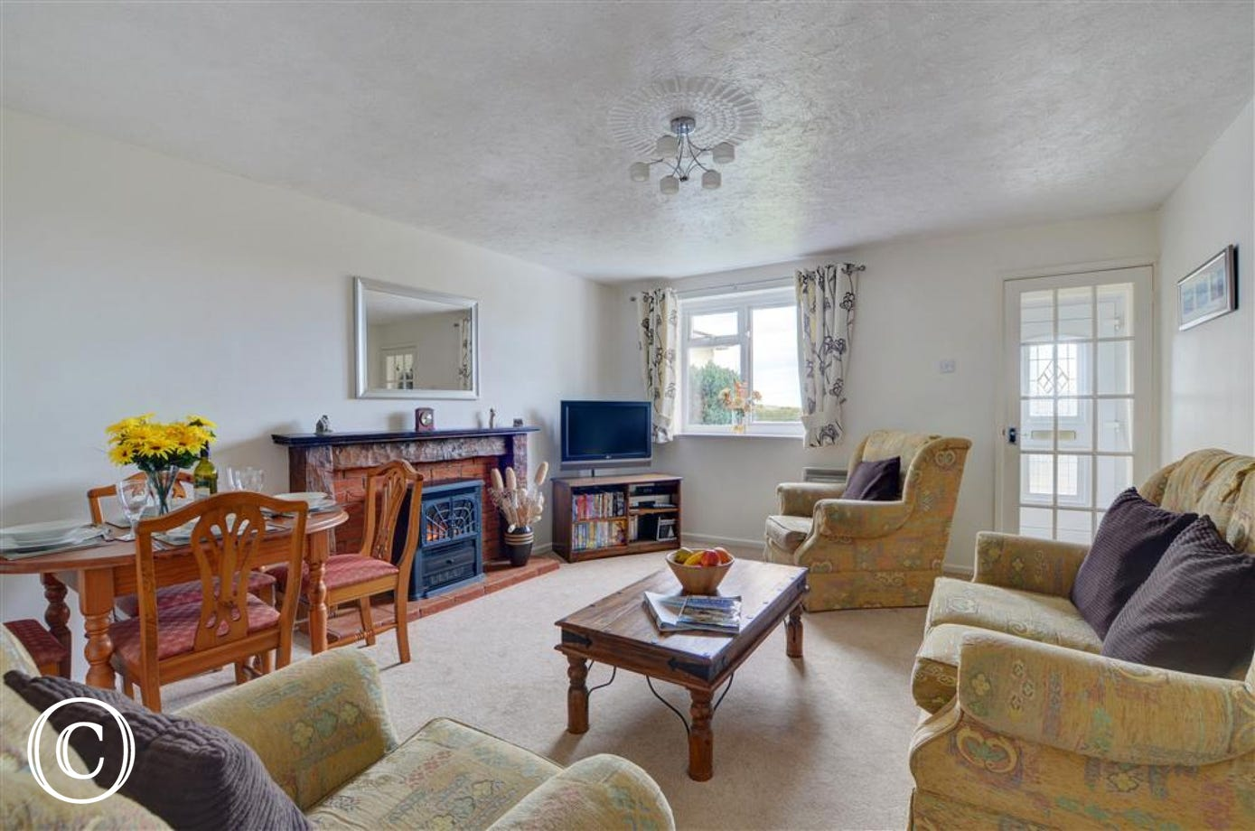 The good sized and very comfortable living/dining room offers views over the village and out towards the sea