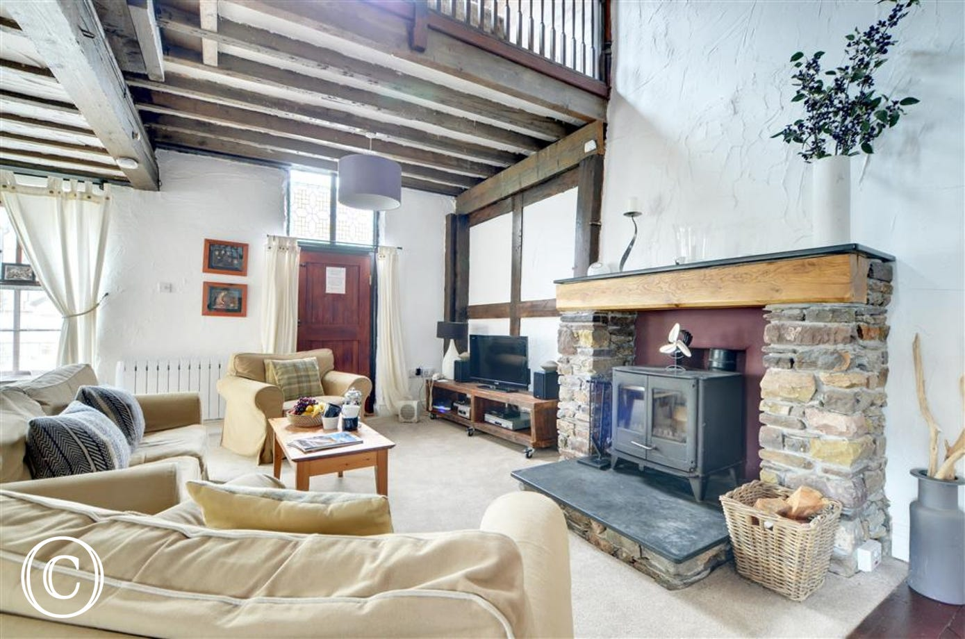 Lovely open plan space showing off all the traditional features, exposed beams, sloping ceiling and a wonderful fireplace with a log burner.
