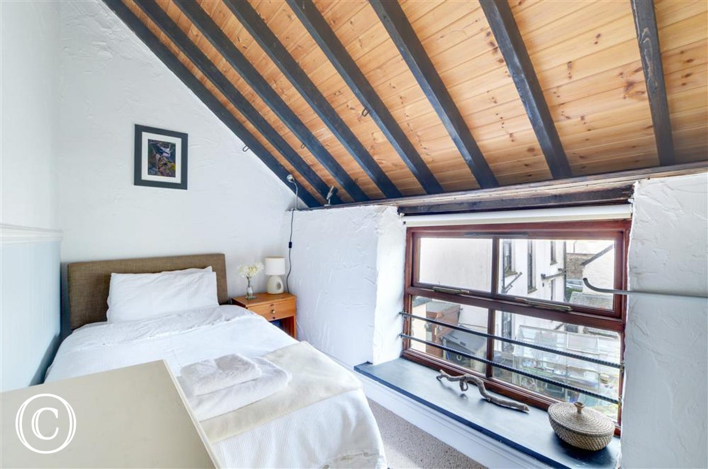 Single room with sloping ceiling and exposed beams.