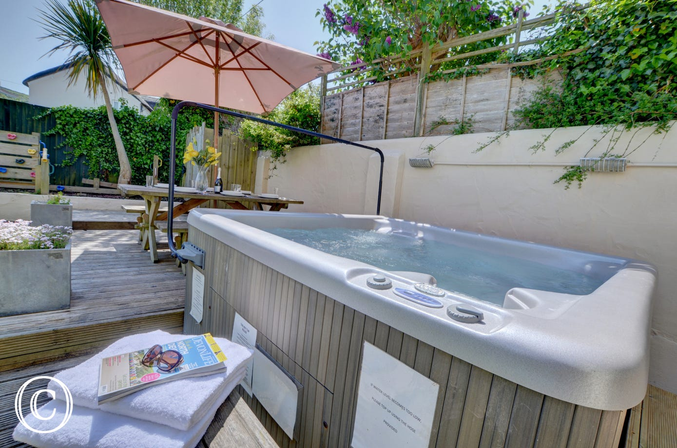 Decking leads around the side of the lawn to the delightful hydro massage hot tub