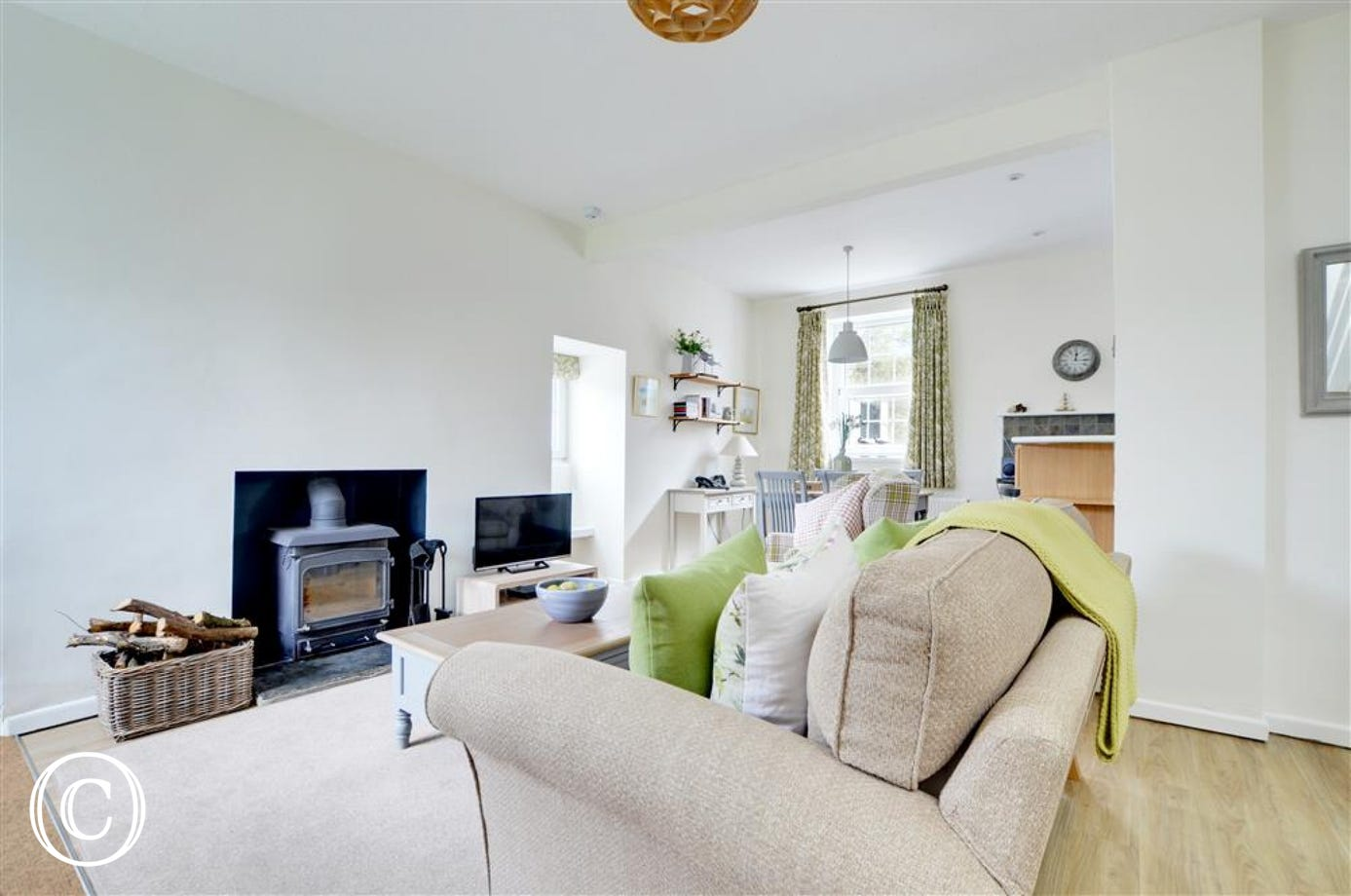 Comfy sofas surround an attractive feature fireplace with wood burning stove, perfect for cosy evenings at any time of year