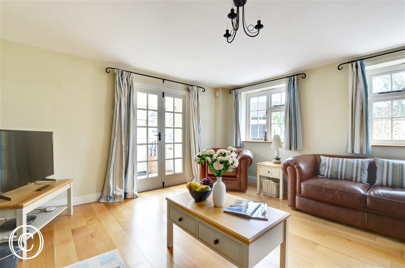 Stylishly presented sitting room with leather sofas and a large TV