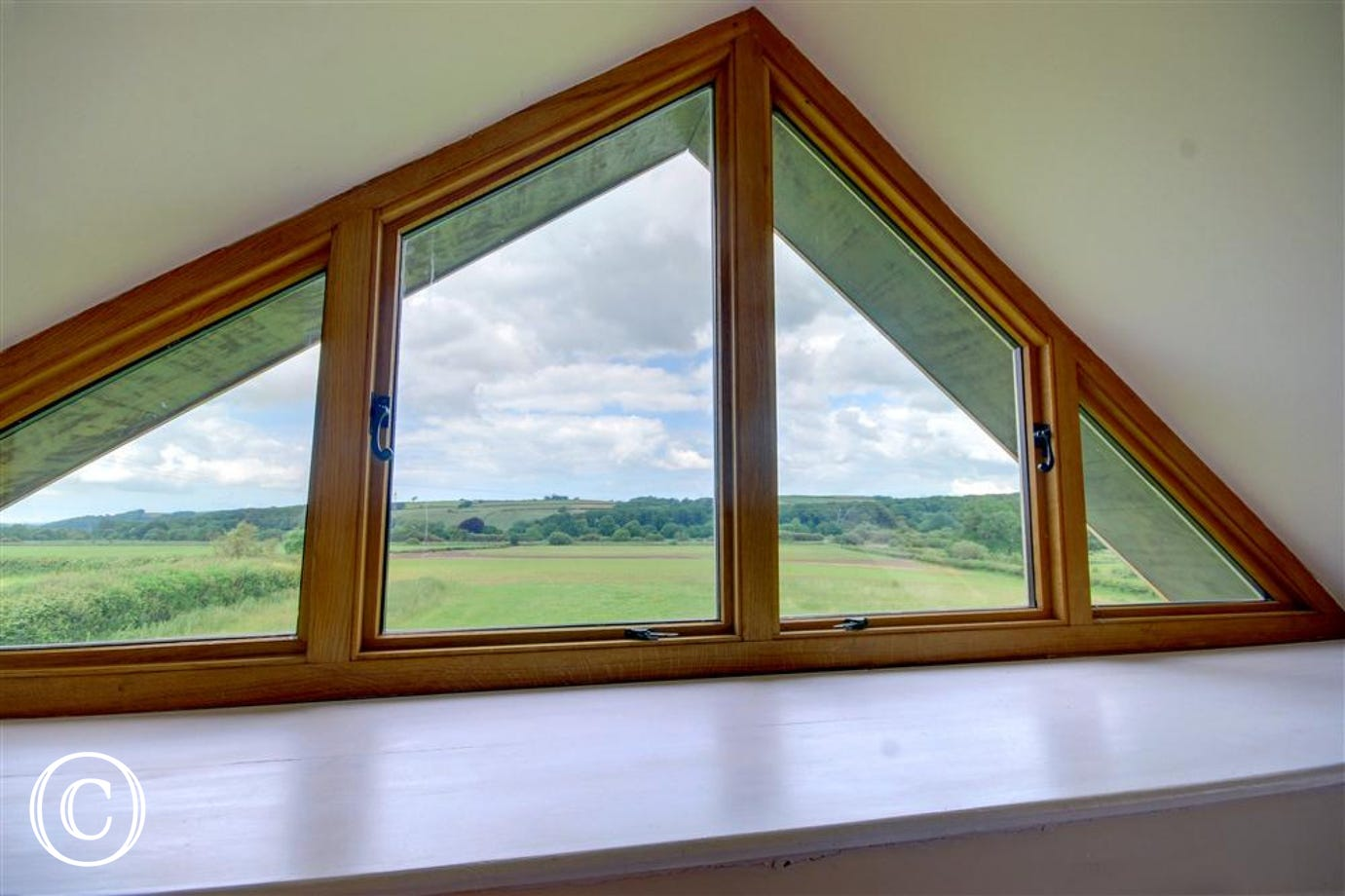 This unique window frames the stunning panoramic countryside scene