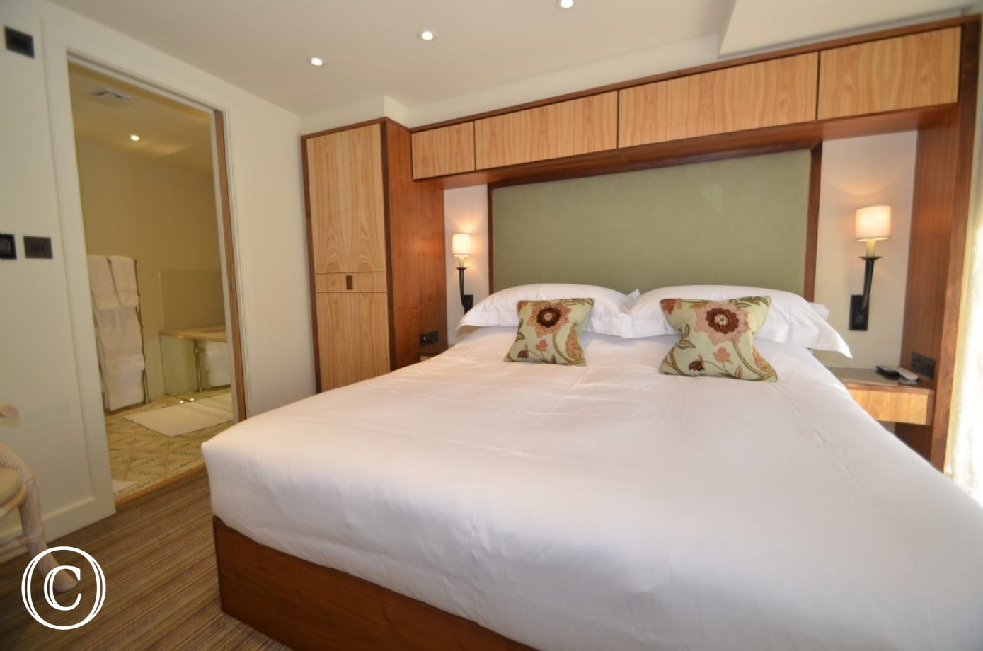 Bedroom two, the Master-Suite is situated up the gorgeous wooden spiral staircase to the first floor. Consisting of a kingsize bed with fitted wardrobes and drawers. Two bedside lamps and a small wall-mounted flat-screen TV.