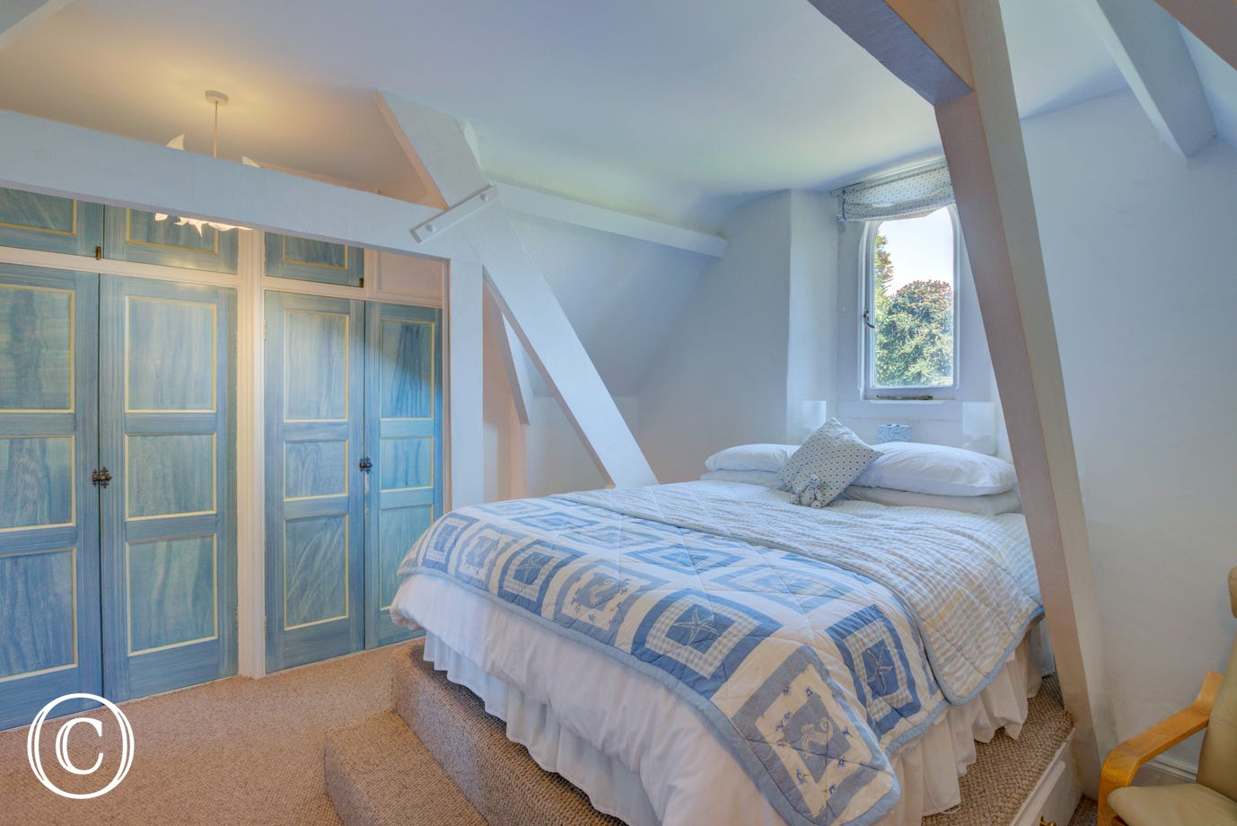 Bedroom One is furnished with a raised double bed, built in wardrobes and a chest of drawers.  There is a sloping ceiling and exposed beams.  A gothic window offers countryside views.