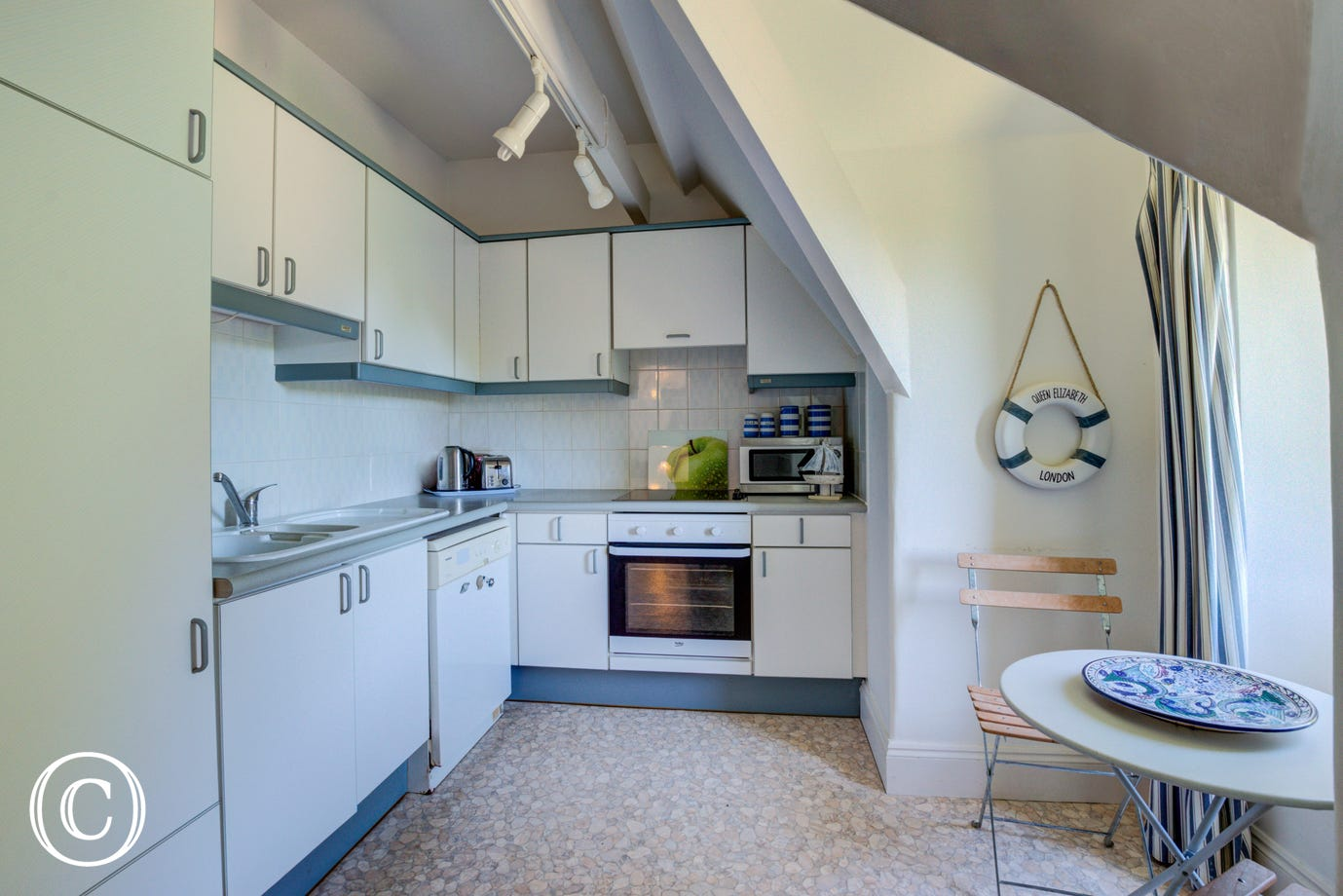 An open archway leads into the kitchen furnished with a range of base and wall units with a built under electric cooker and hob, larder fridge with ice compartment and a dishwasher.
