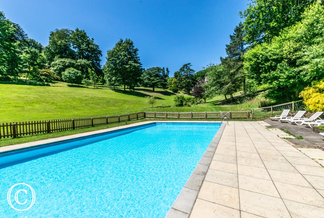 Within the grounds sits an outdoor heated swimming pool