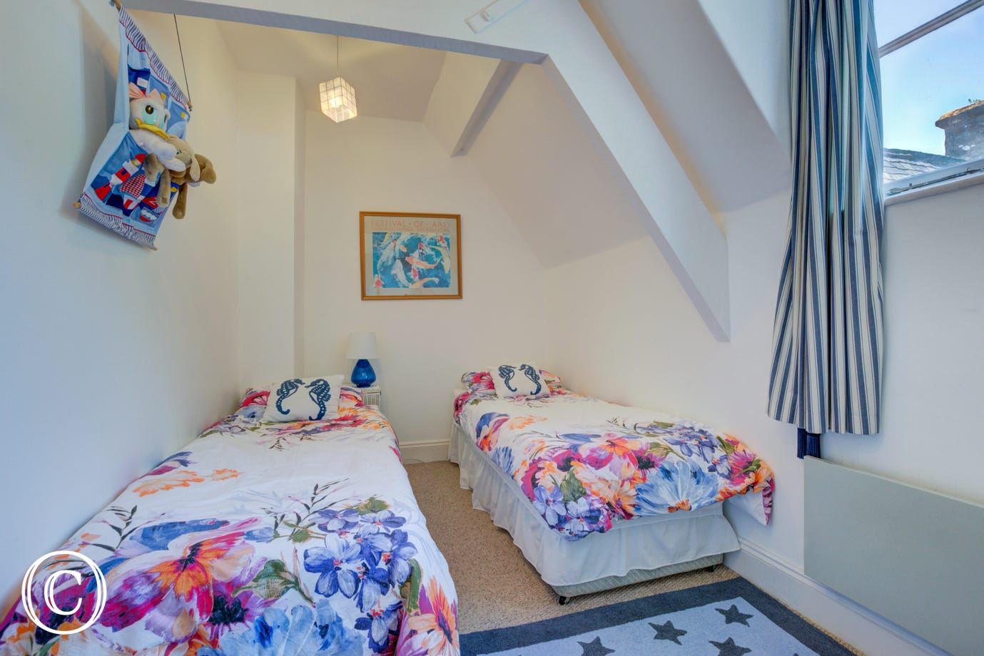 Bedroom Two is furnished with zip and link single beds and chest of drawers units.  There is a sloping ceiling and exposed beams. A window to the rear gives views over the inner cobbled courtyard.