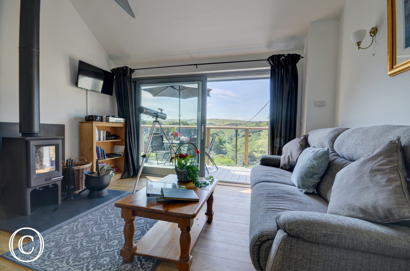 Comfortable sofa, woodburner and lovely views from the open plan living area