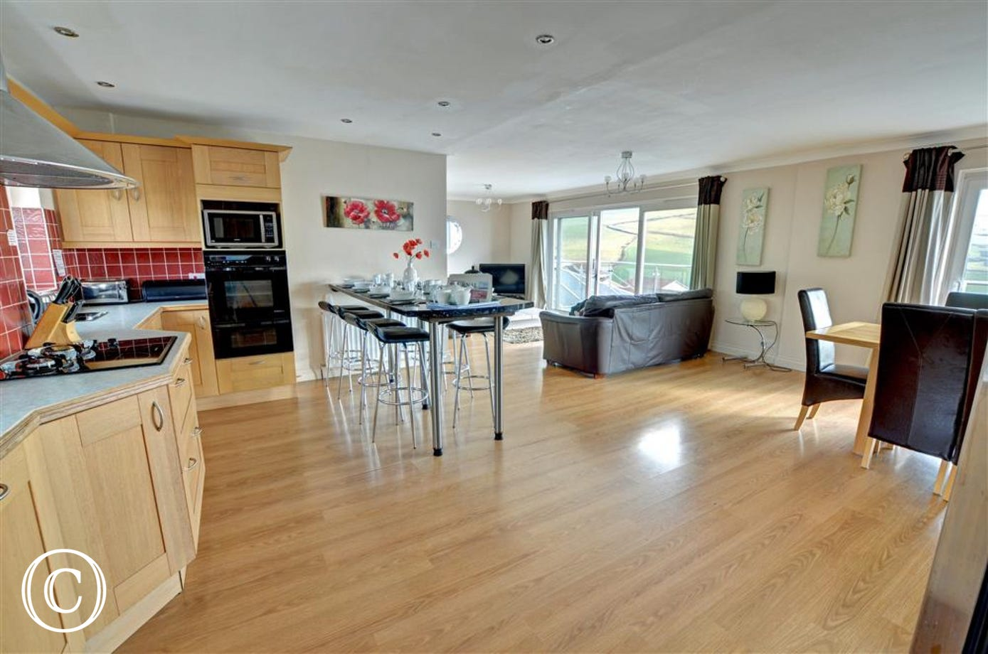 A spacious open plan living area with attractive fitted kitchen and comfy leather sofas opens onto a stunning glass fronted balcony