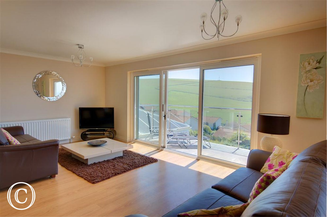 The spacious sitting room with patio doors opening out to the top balcony