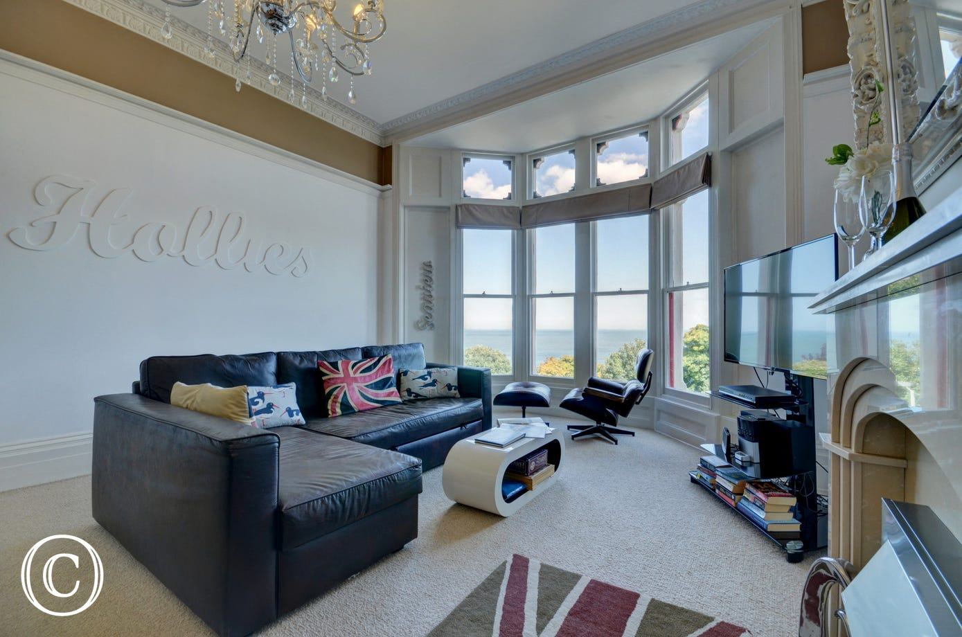The spacious living/dining room with attractive fireplace and excellent sea views has a large comfy leather sofa