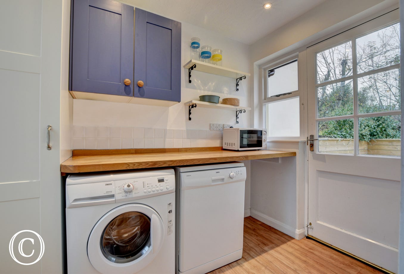 The useful utility room with dishwasher and washer/dryer is just off the kitchen