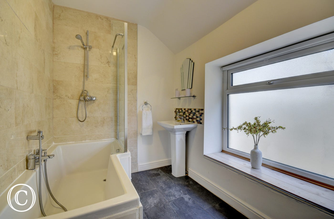 The contemporary family bathroom contains a bath with shower overhead and this room has a heated ceramic tiled floor