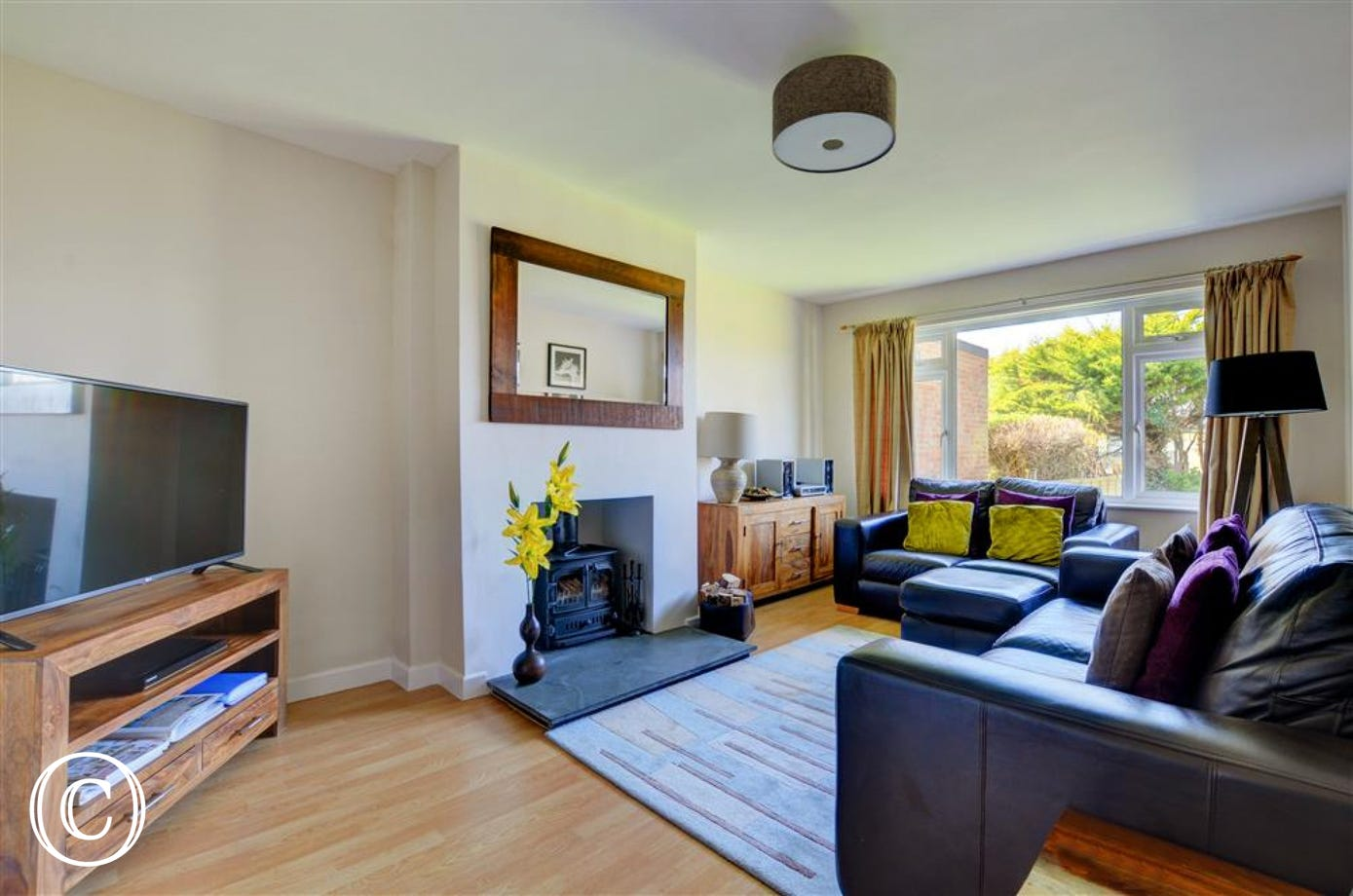 Wood laminate flooring and comfy leather sofas round a slate fireplace make this a cosy and welcoming sitting room
