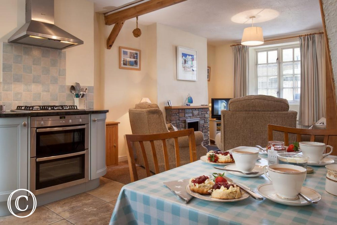 Open plan inviting spacious holiday cottage with kitchen area, dining area and living room in one bright and welcoming space
