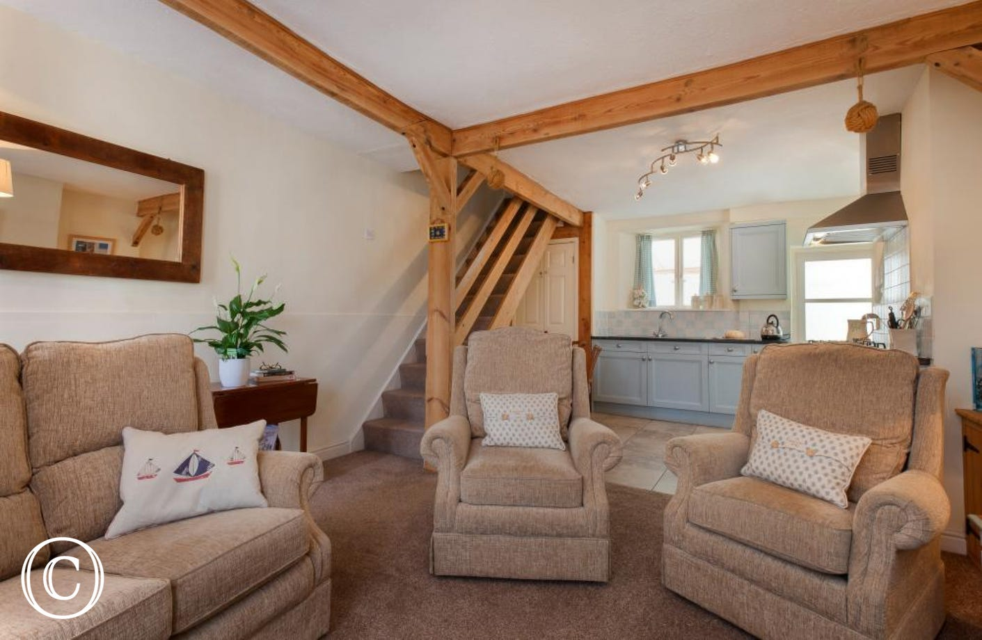 Comfy living area with large soft sofas and seaside theme cushions in Shaldon holiday cottage