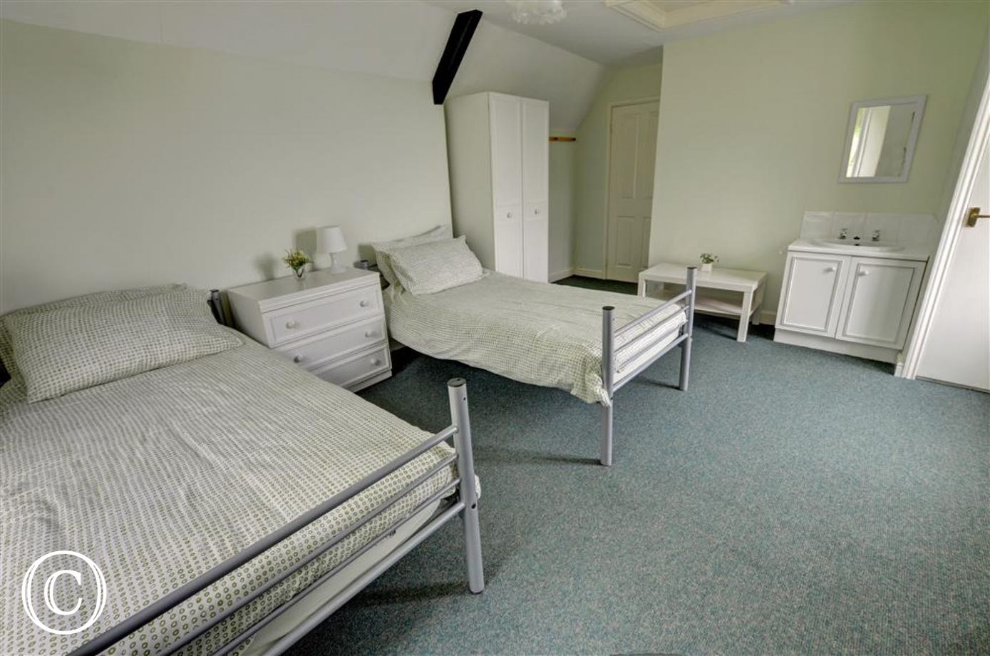 Spacious and comfortable twin bedroom with hand basin.