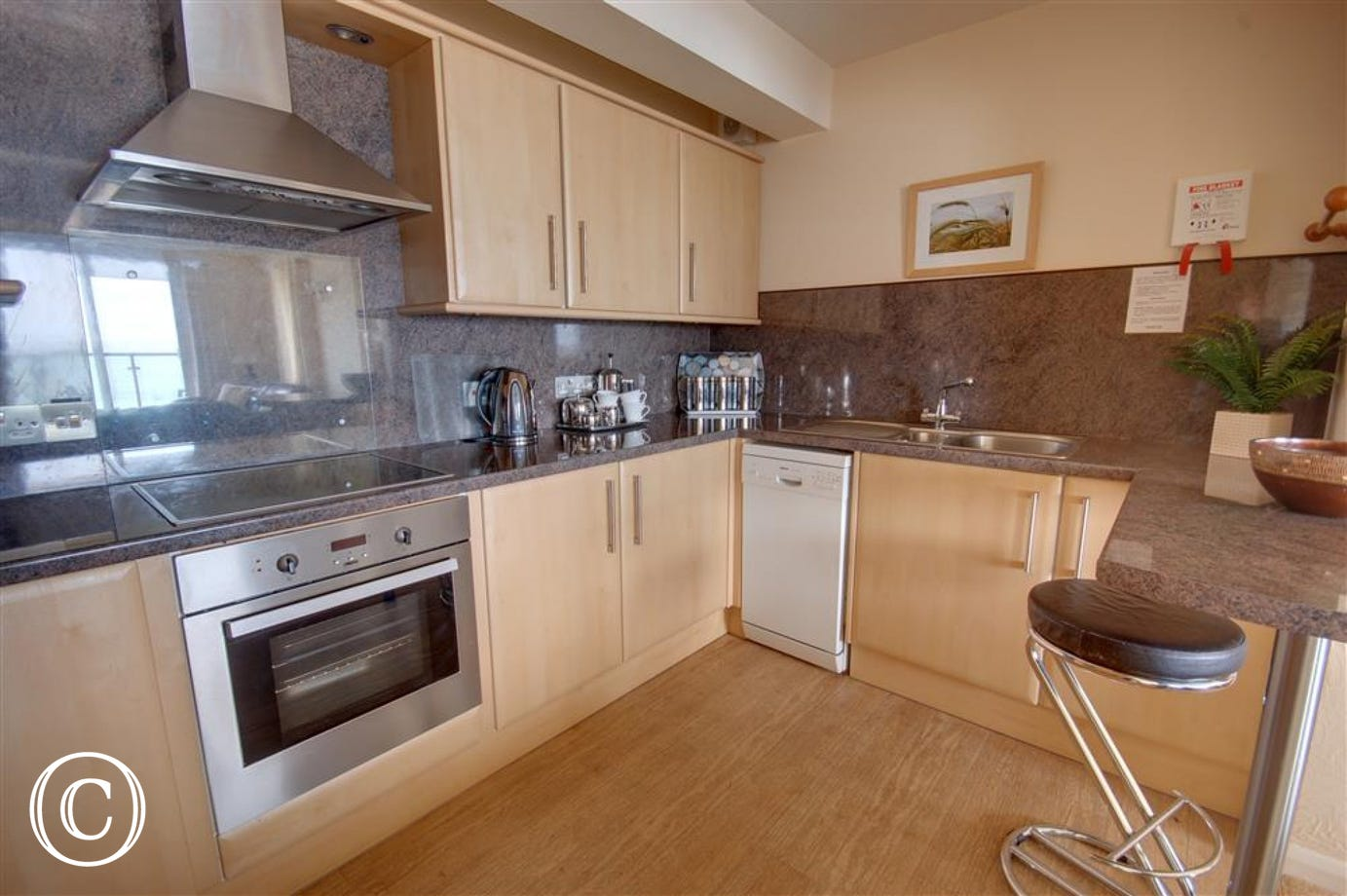 A modern stylish well equipped and fully fitted maple kitchen to the rear and has patio doors to a balcony