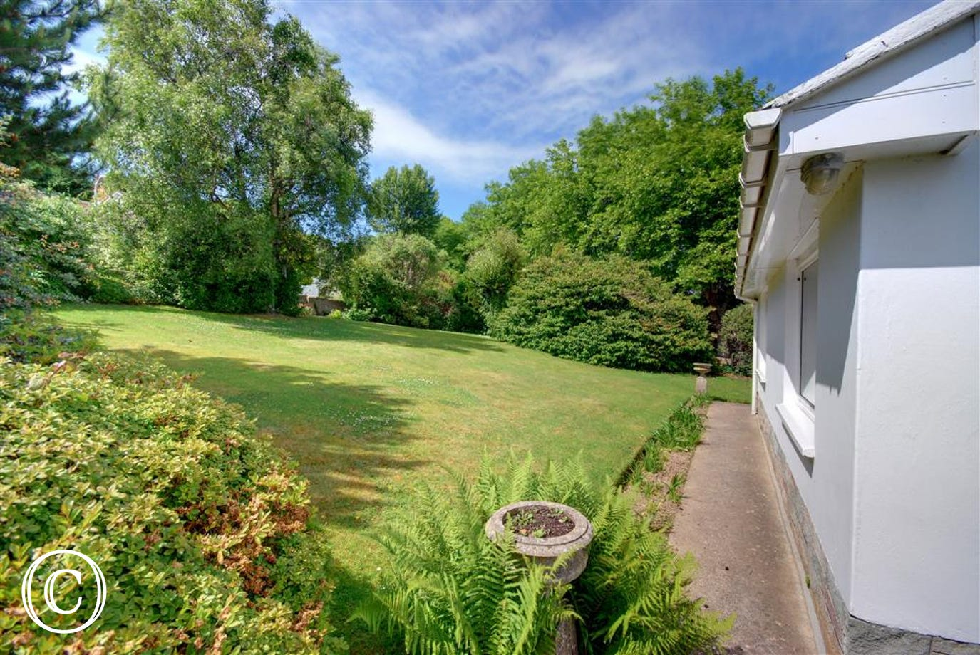 The property is surrounded by mature gardens and slightly sloping lawn