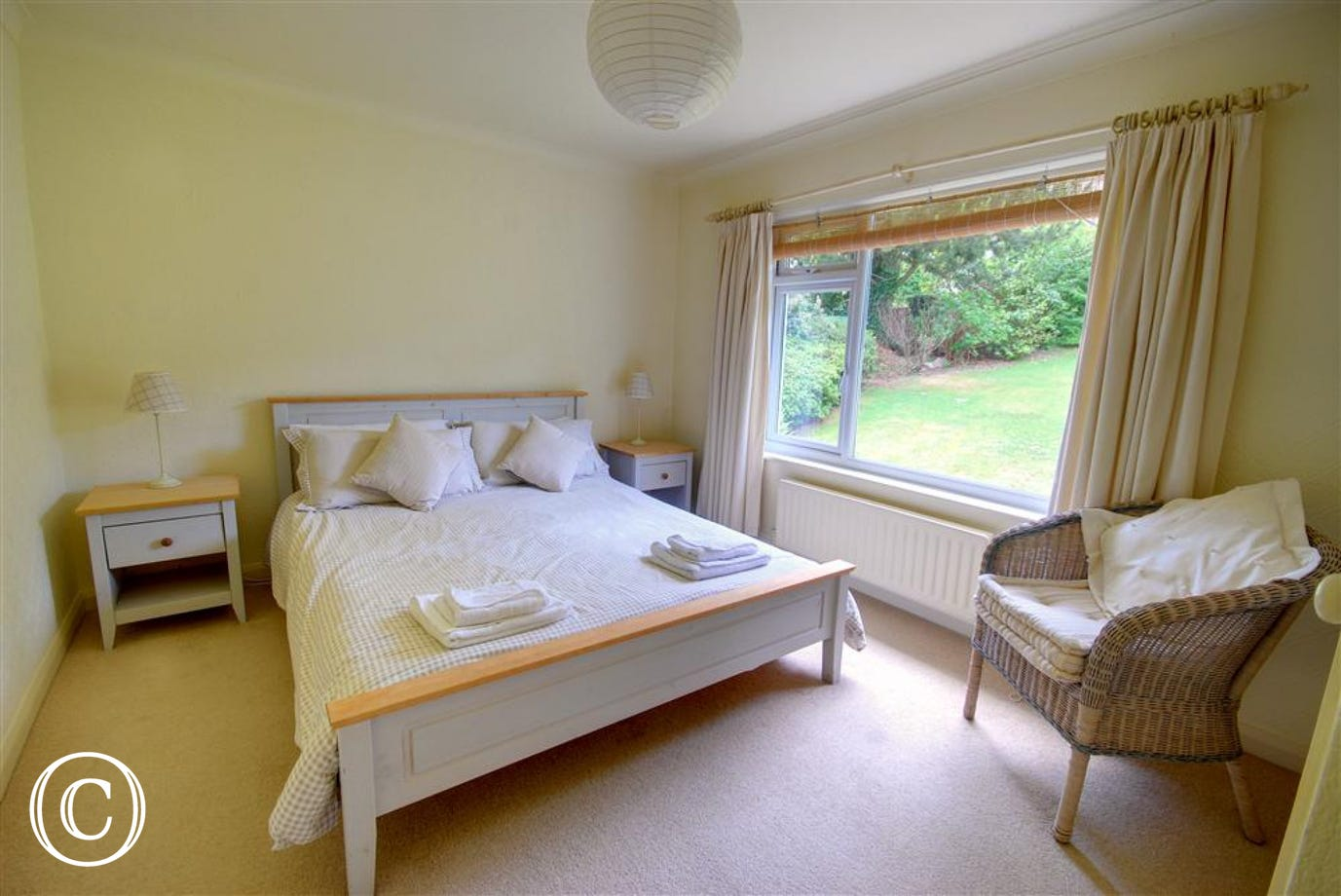 Simply decorated double bedroom with a large picture window and views over the garden