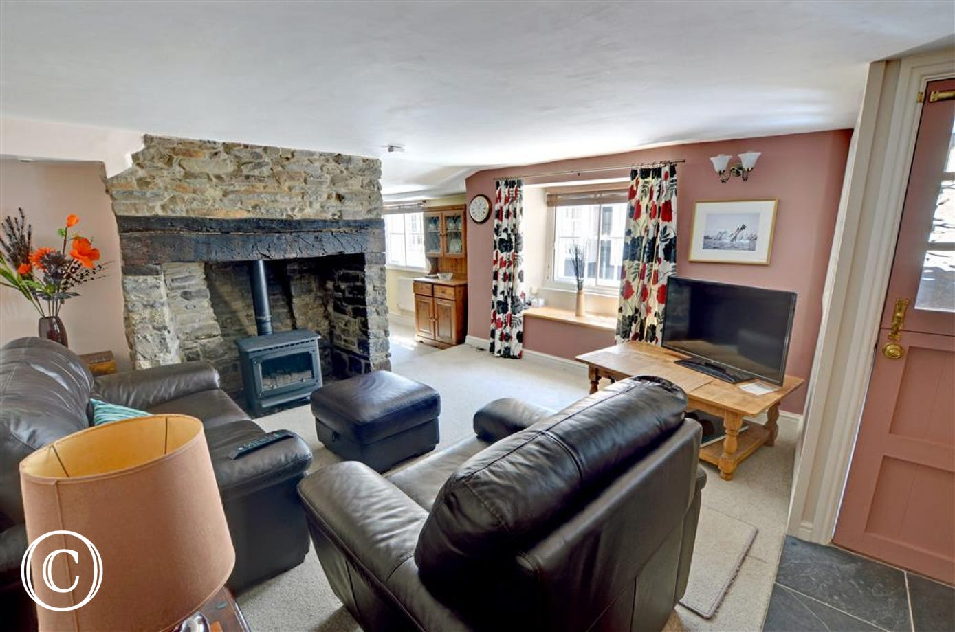 Living/dining room with low ceilings and a centre piece stone fire place with gas effect log burner