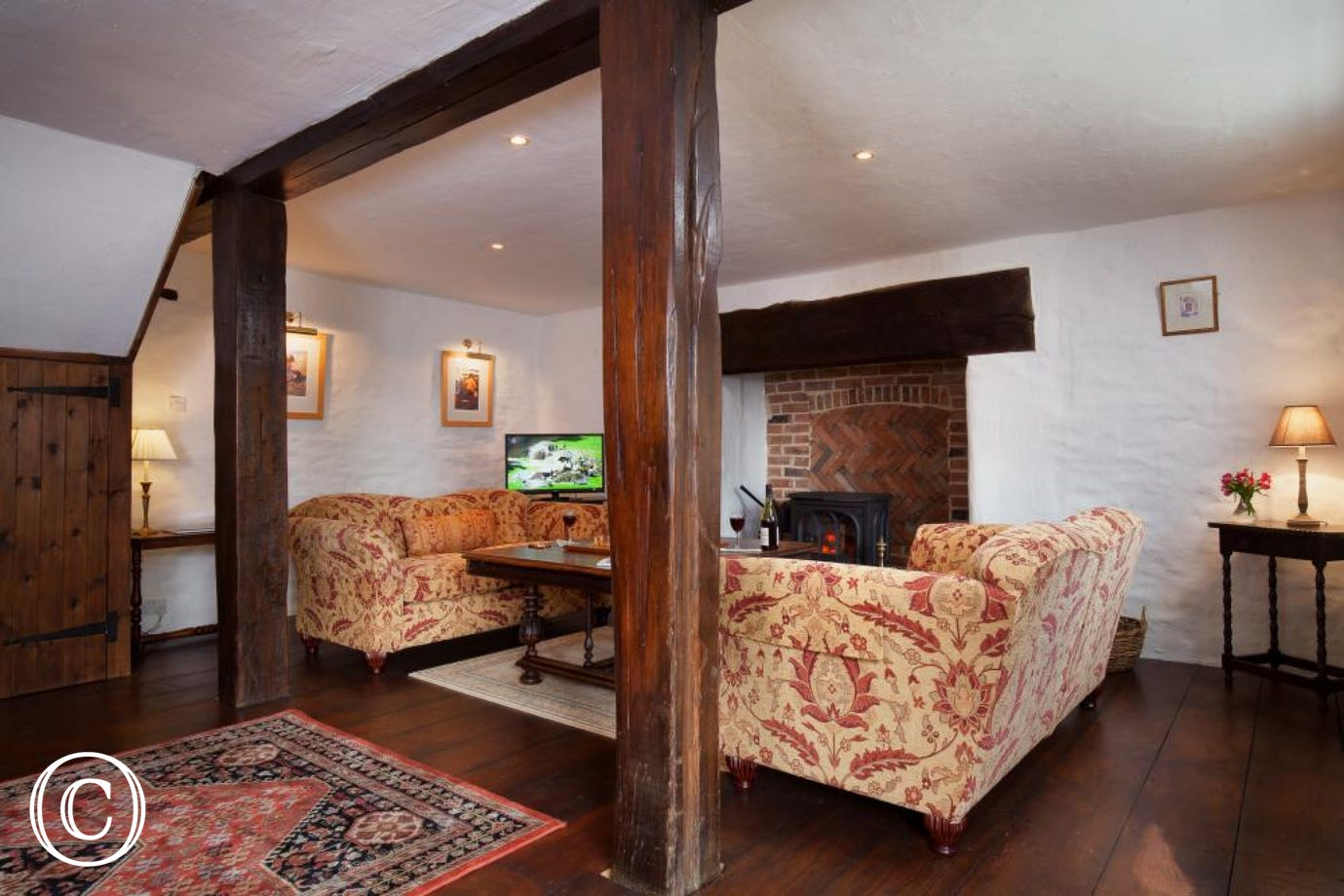 Spacious living area with wood burner at Hutchinghayes Barn, Combe Raleigh