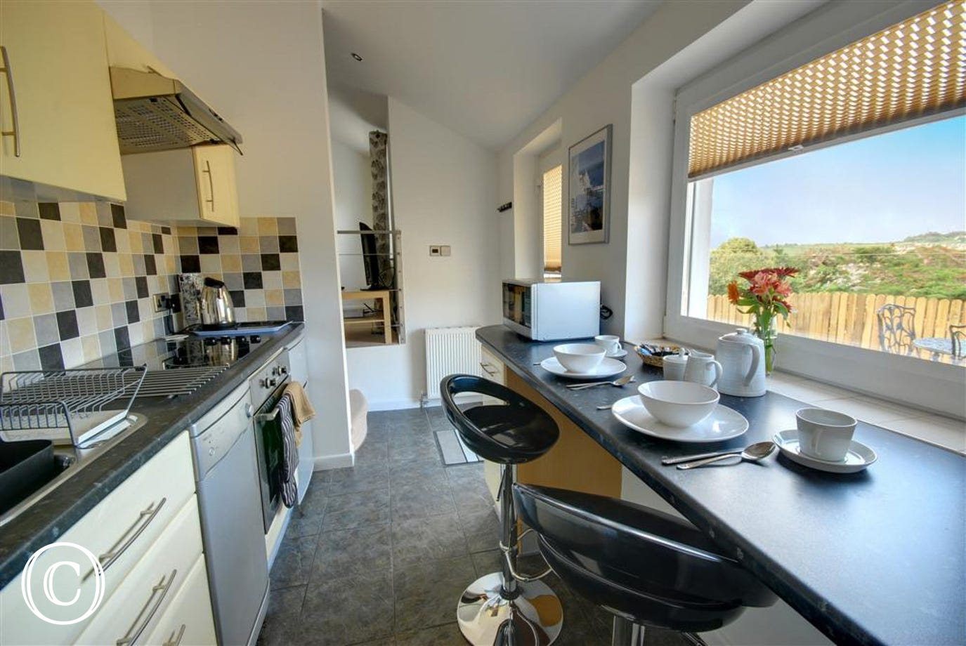 The lovely modern kitchen with breakfast bar over looking the patio
