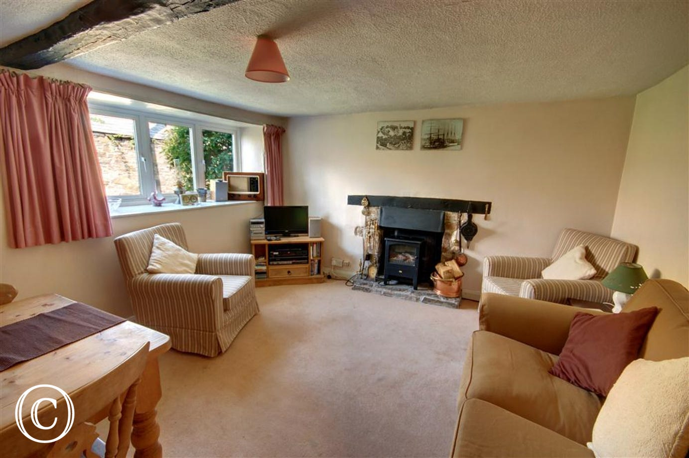 This cosy sitting room with open stone fireplace, its great for unwinding after a day exploring the nearby coastline.