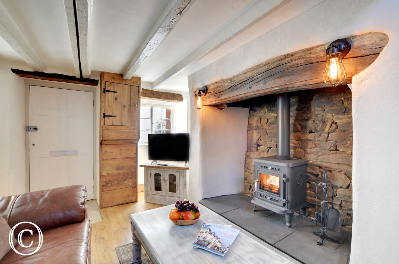 The front door opens directly into an open plan living space with low beams and a woodburner for the cooler seasons