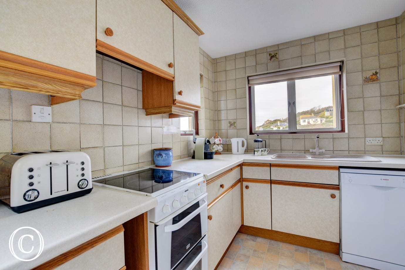 Kitchen: Excellent sea views. Oven with grill and a four ring hob, microwave, fridge/freezer, dishwasher and a good range of cooking utensils.