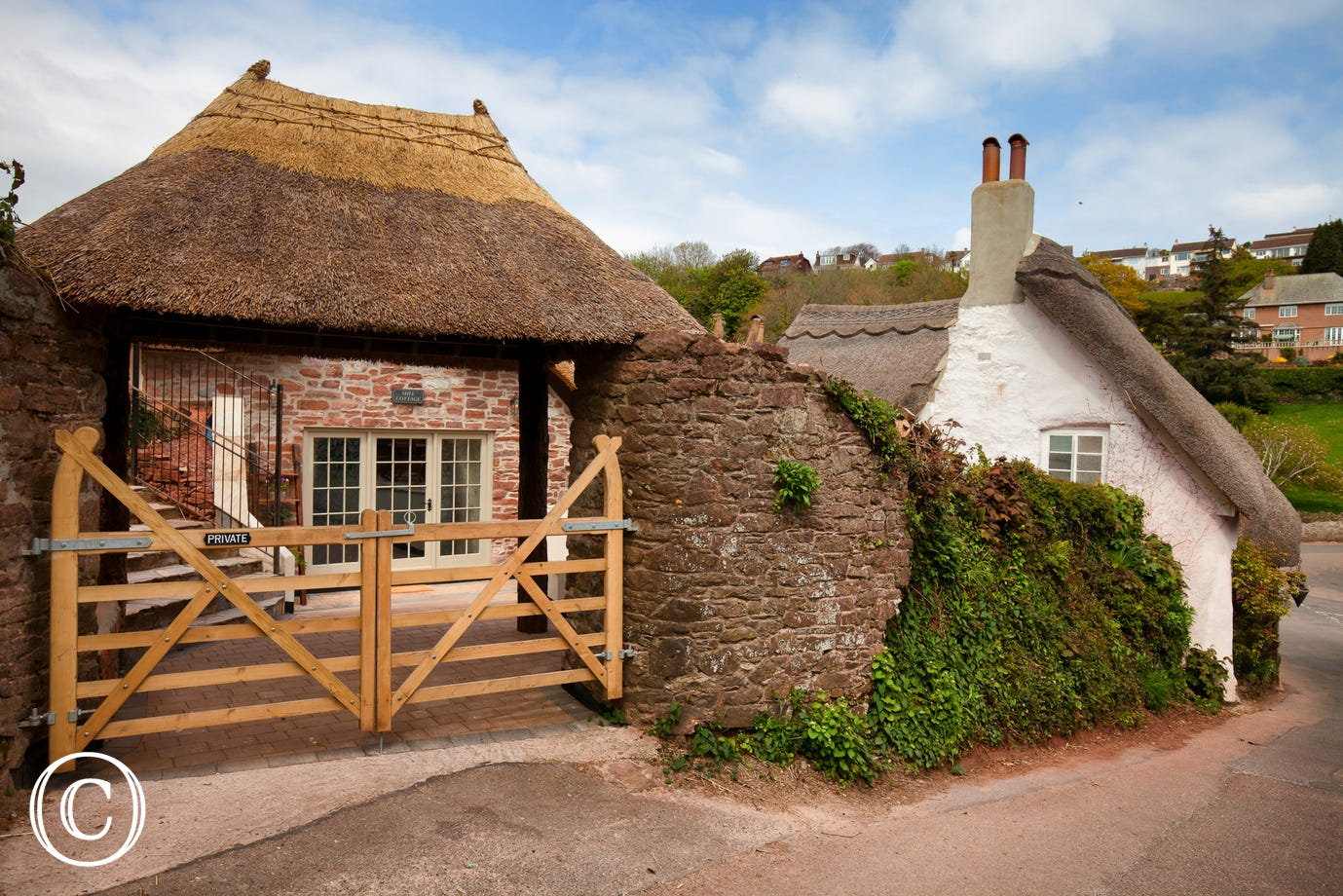 private entrance to Mill Cottage Cockington, with thatched archway and private driveway parking