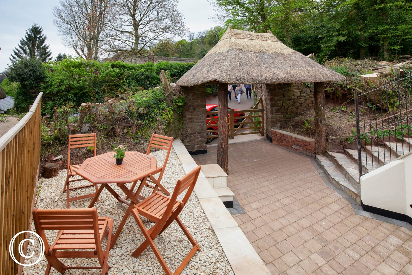 Alfresco dining on the sun trap gravelled terrace with wooden table and chairs