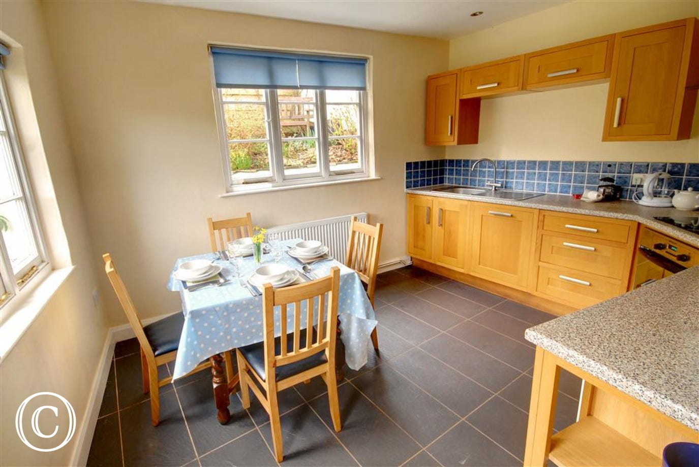 The modern kitchen features a slate tiled floor complimented by granite style worktops and is well equipped for all your needs