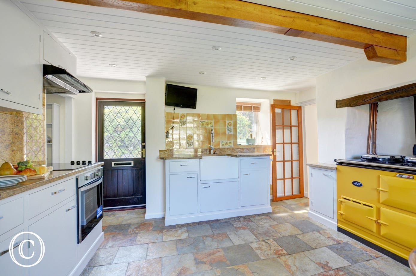 The attractive kitchen which benefits from a slate floor and granite worktops and brightly coloured AGA