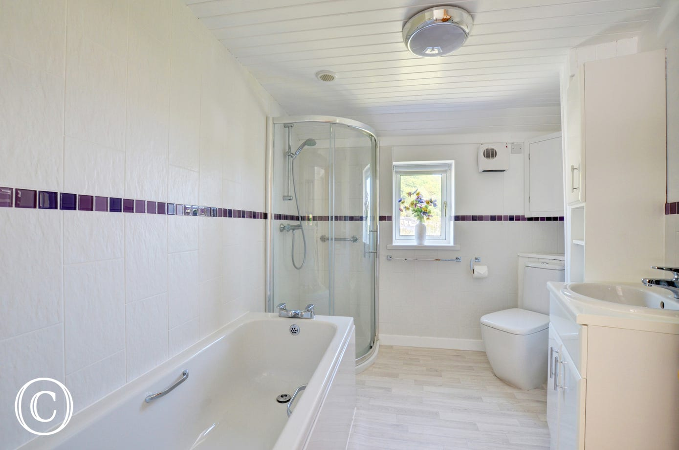 The bathroom has a stained glass window, a bath, shower cubicle, heated towel rail, basin and WC