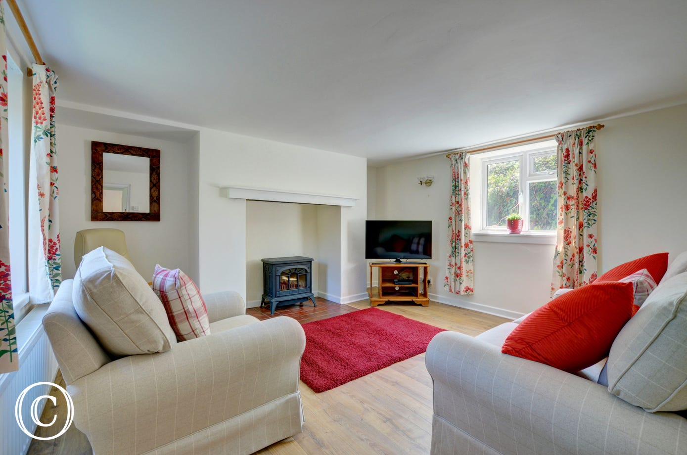 The living room has comfy seating in front of a gas effect woodburner and smart TV