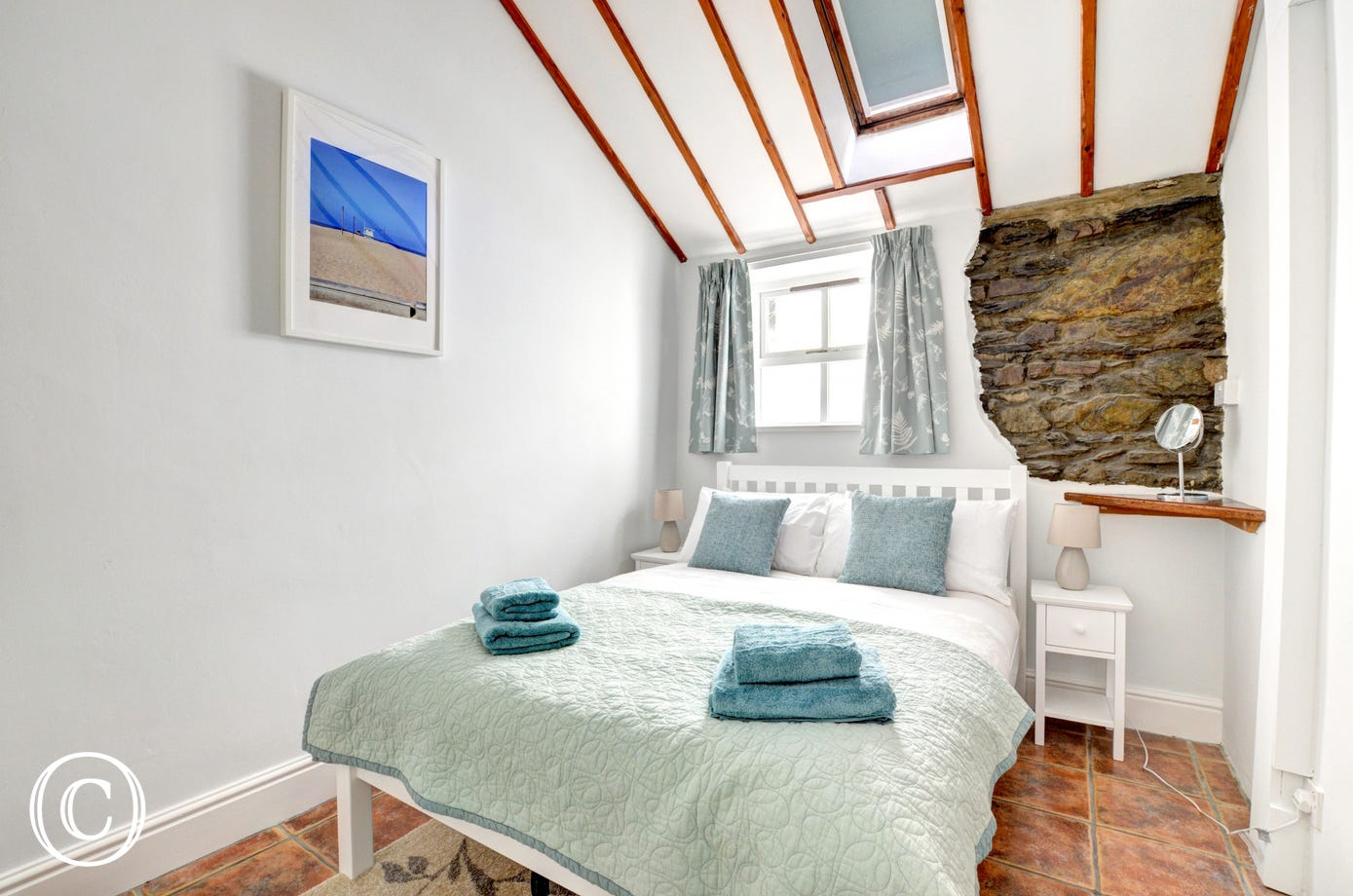 Tastefully decorated double bedroom with exposed stone wall