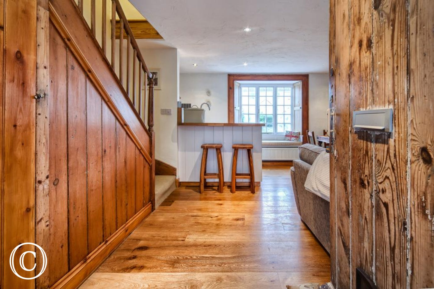 true devon cottage with welcoming wooden door, solid wood floors and bright window in the background