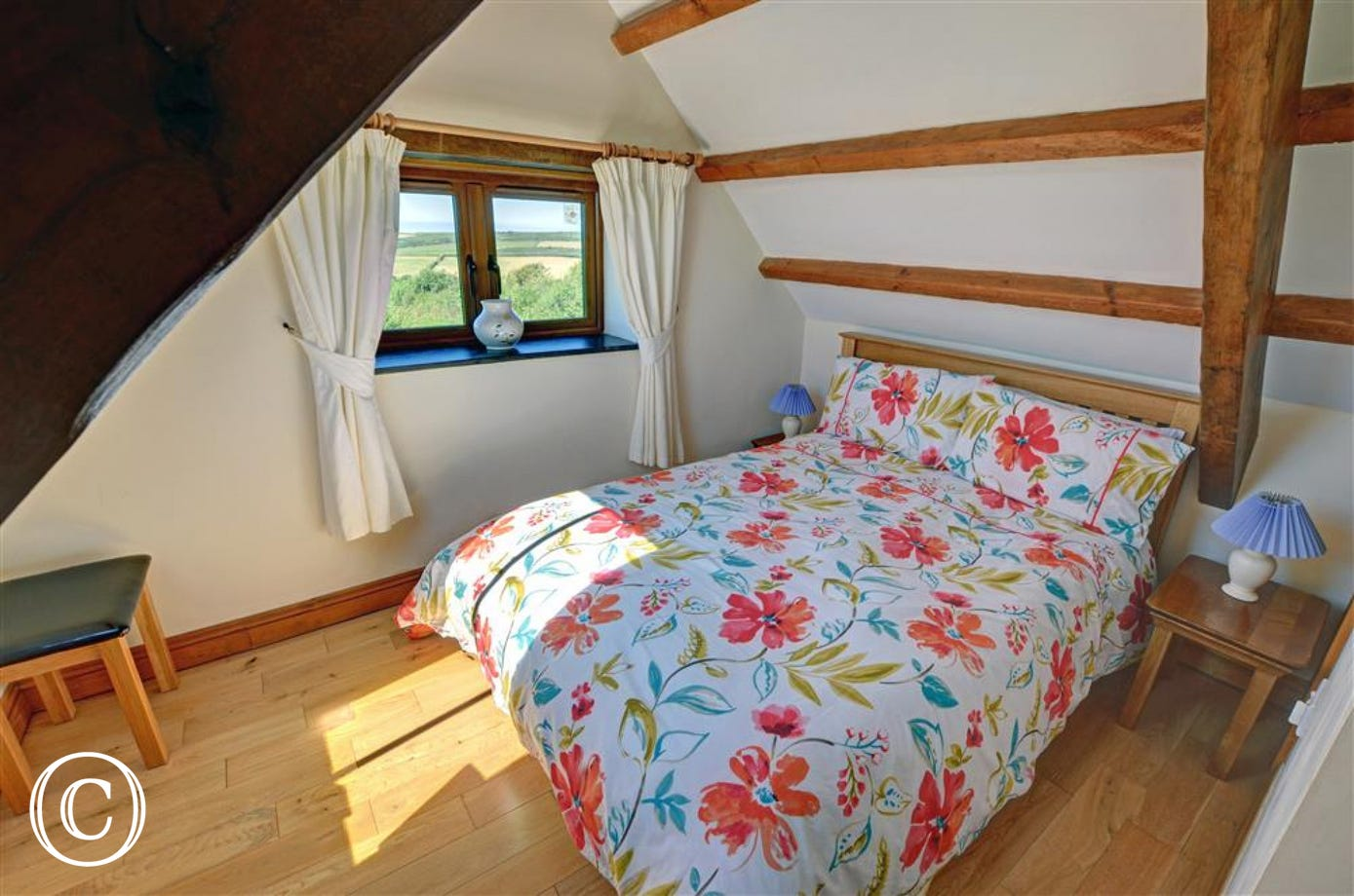 A pretty beamed and vaulted bedroom has distant sea views and an en-suite bathroom