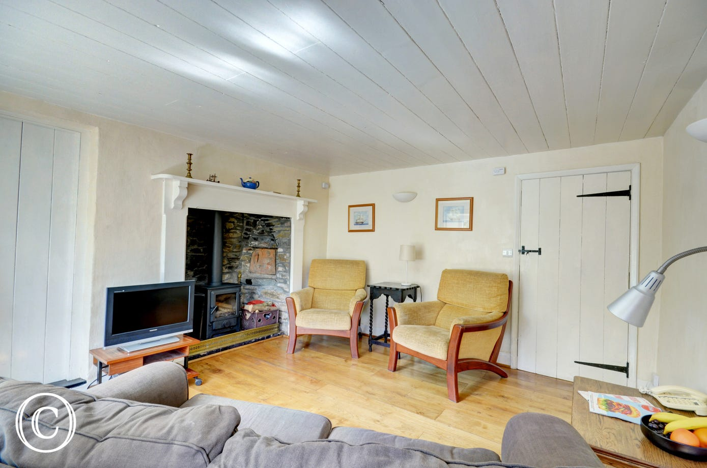 The cosy living room with inglenook has a wood burning stove, lovely at any time of year