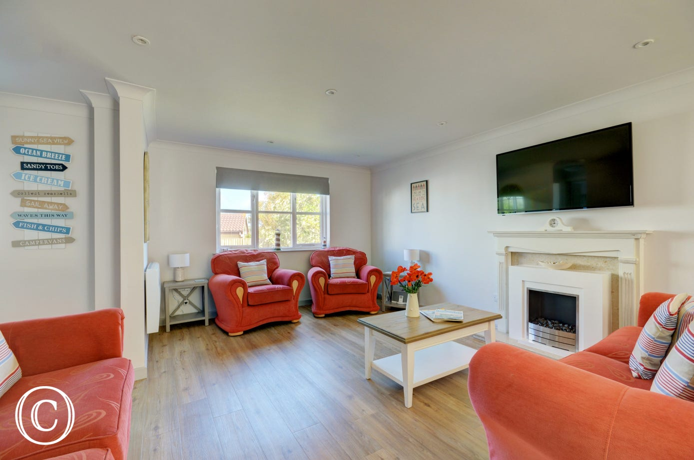 The stylish living/dining room has comfy sofas surrounding the fireplace and patio doors leading onto the patio