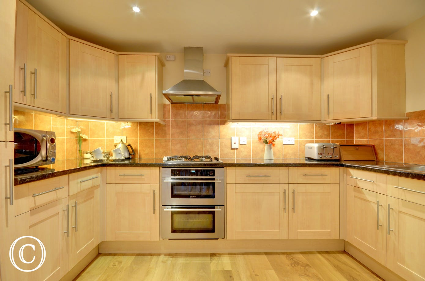 Maple units and granite style work surfaces complement the kitchen and dining areas to the rear