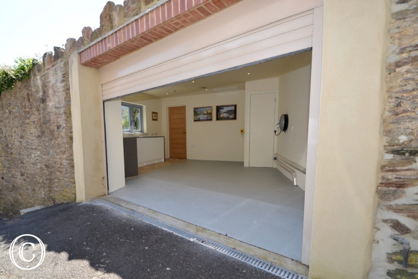 The garage is situated next to the main gate to the house. The white electric door is operated from inside the property and can be found on the first floor. There is room for one average sized car. There is also a fast charge electric pod point for an ele