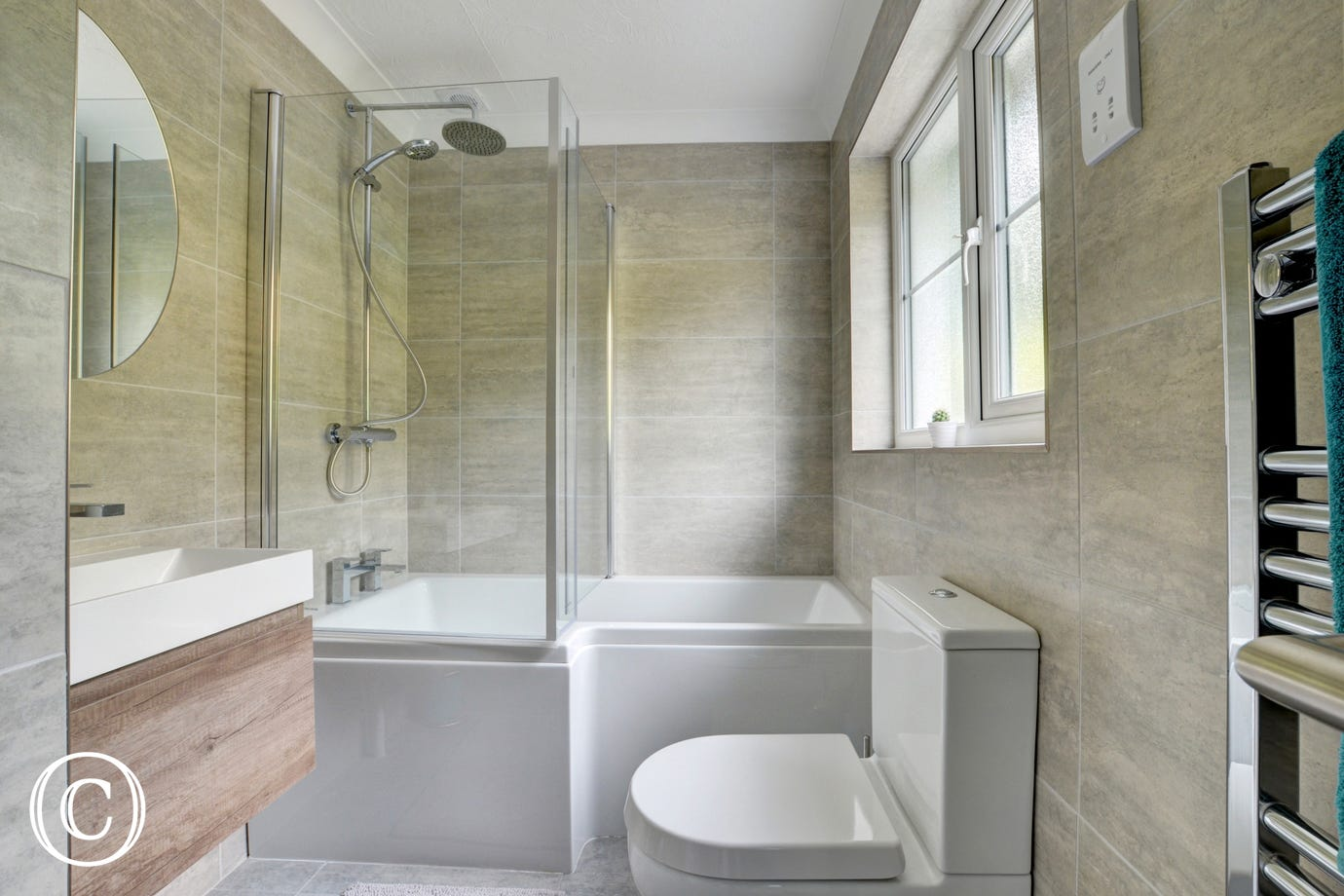 The family bathroom has a fully enclosed shower over the bath, WC, basin and heated towel rail